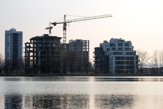 Guindastes de torre e altos edifícios de apartamentos residenciais em construção na margem do lago. desenvolvimento imobiliário.