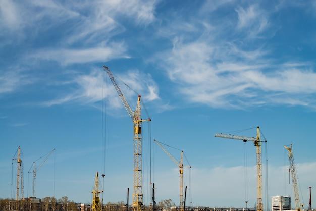 Guindastes de torre grandes acima das construções sob a construção contra o céu azul.