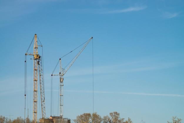 Guindastes de torre grandes de encontro ao céu azul.