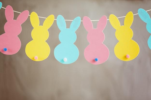 Guirlanda com coelhos de papel colorido. banner de coelhinho da páscoa de conceito