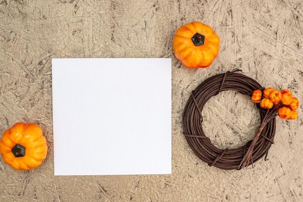Guirlanda de abóboras com frutas e papel em branco em madeira compensada