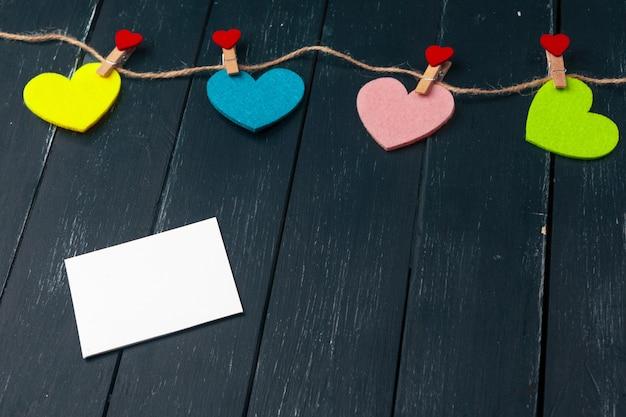 Guirlanda de corações de papel em fundo preto de madeira
