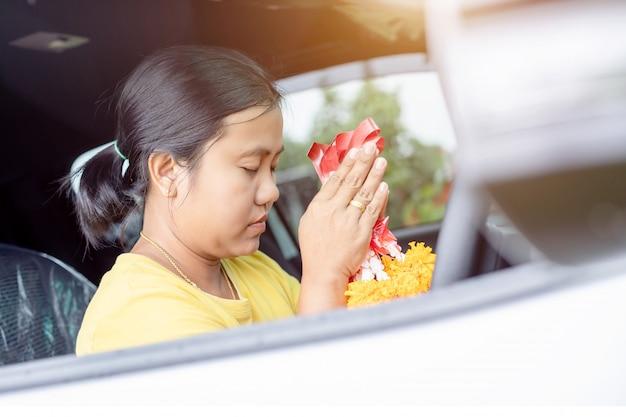Guirlanda de flores de mulher na mão e rezando no carro novo para luckythe novo carro para a sorte