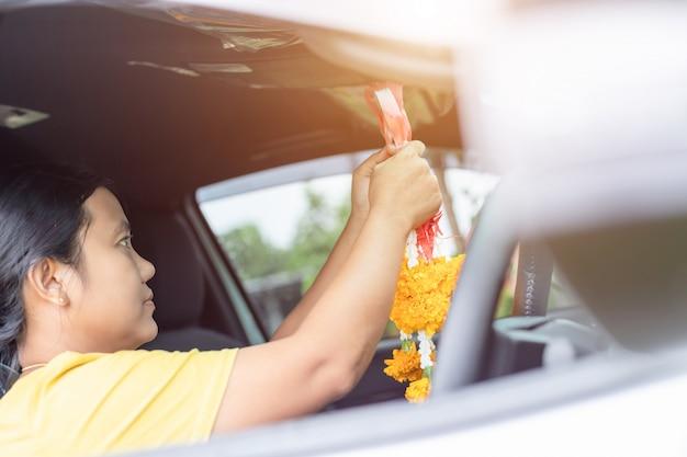 Guirlanda de flores de mulher na mão e rezando no carro novo para sorte