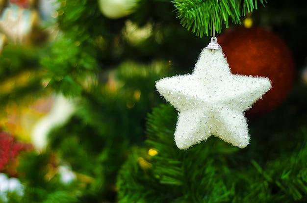 Guirlanda de natal, bolas, luzes, brinquedos, figura decorativa branca estrela de prata na árvore de natal. decoração de casa no ano novo.