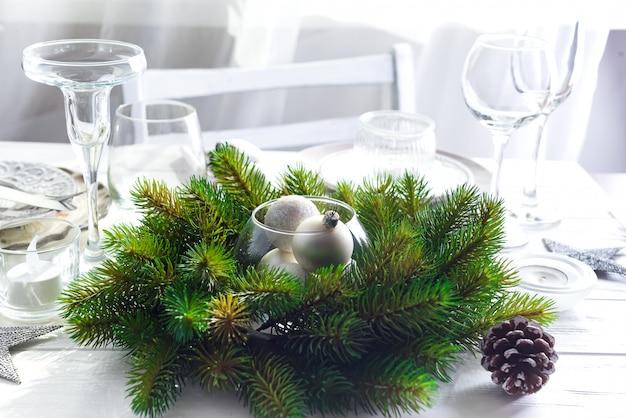 Guirlanda de natal com brinquedos na mesa com configuração de mesa de natal prata