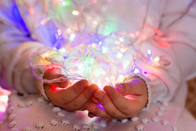Guirlanda de natal de lâmpadas led multicoloridas nas mãos de uma criança vestida com uma camisola de malha branca.