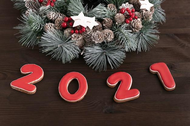 Guirlanda de natal e biscoito de gengibre de inscrição 2021. fundo de madeira. fechar-se.