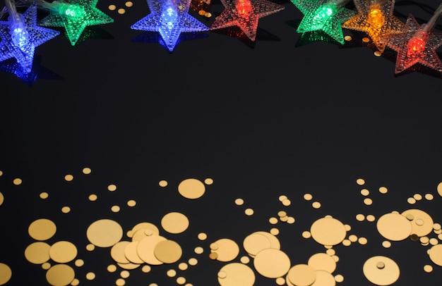 Guirlanda de natal em forma de estrelas confetes dourados sobre um fundo preto decoração de natal