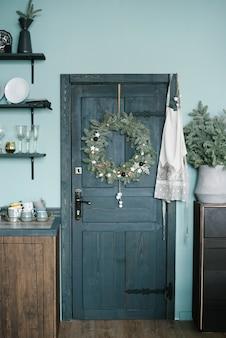 Guirlanda de natal na porta de madeira da cozinha em estilo escandinavo em tons de azul