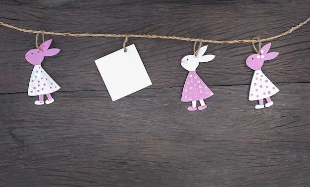 Guirlanda de páscoa com coelhos e cartão em branco em um fundo de madeira.