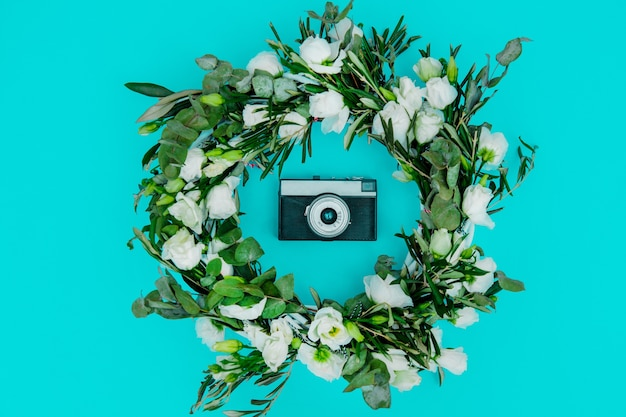 Guirlanda decorada com rosas brancas e câmera vintage sobre fundo azul. decorado. acima vista