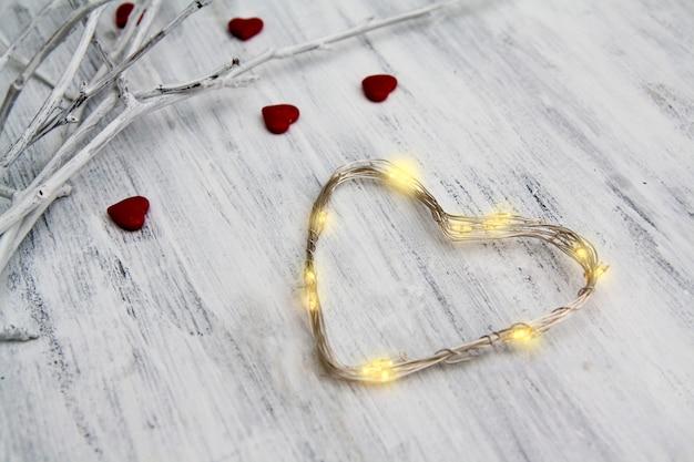 Guirlanda em forma de coração na mesa de madeira branca. perto de galhos brancos com corações vermelhos. foto do conceito para o amor e dia dos namorados