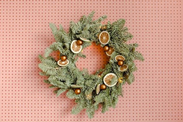 Guirlanda festiva feita de galhos de pinheiro contra a parede