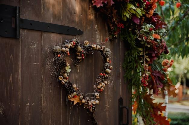 Guirlanda natural em forma de coração na porta marrom