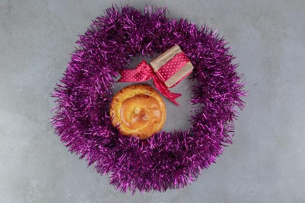 Guirlanda roxa com um pacote de presente e um pãozinho em superfície de mármore