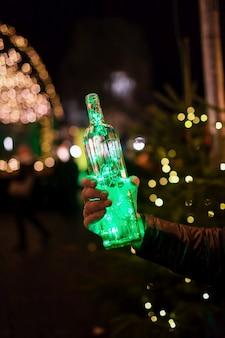 Guirlanda verde na garrafa no fundo da cidade à noite festiva