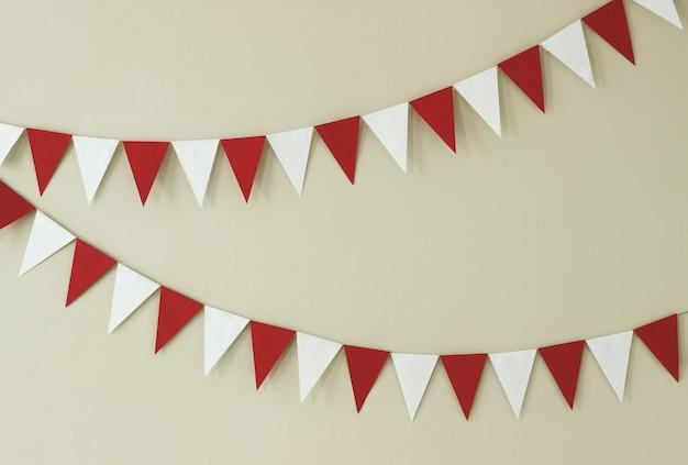 Guirlandas artesanais de papel triangular de branco e vermelho em uma parede de luz.