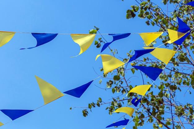 Guirlandas com sinalizadores de feriado triangulares multicoloridos contra o céu azul em dia ensolarado. decoração de bandeiras de festa ao ar livre.