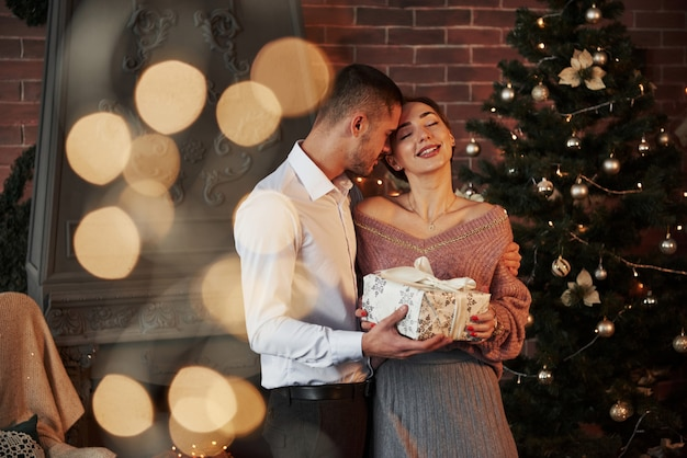 Guirlandas na árvore. presente de natal para a mulher. cavalheiro de terno clássico dá a sua esposa o presente