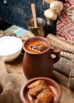 Guisado de carne azerbaijano piti com iogurte, na placa de madeira.