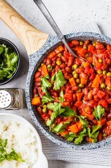 Guisado de feijão vegano com tomate e arroz em uma panela