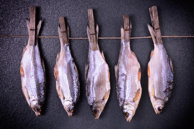 Guisado de peixe seco pendurado em prendedores de roupa em uma corda
