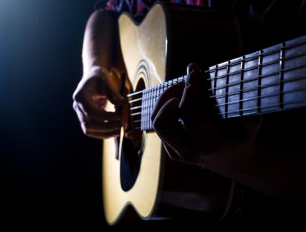 Guitaritst toca o violão no palco.