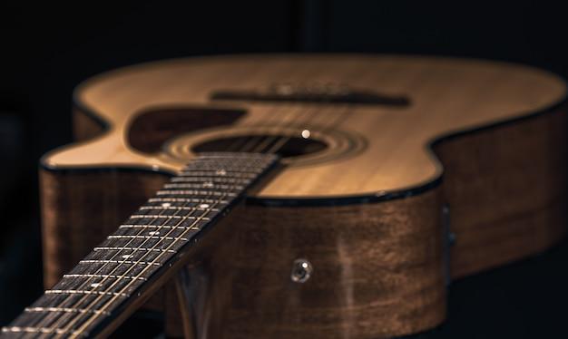 Guitarra acústica com uma bela madeira em um close-up de fundo preto.