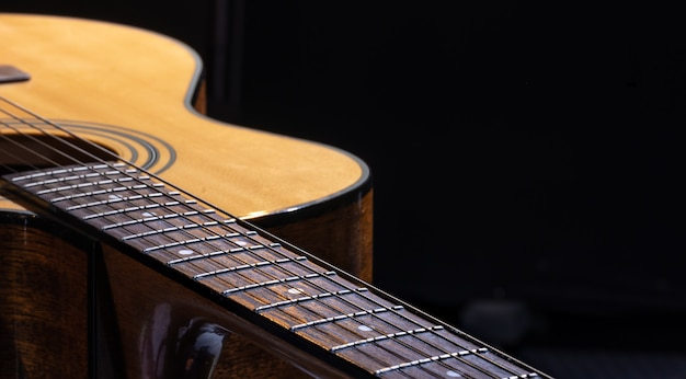 Guitarra acústica com uma bela madeira em um fundo preto.