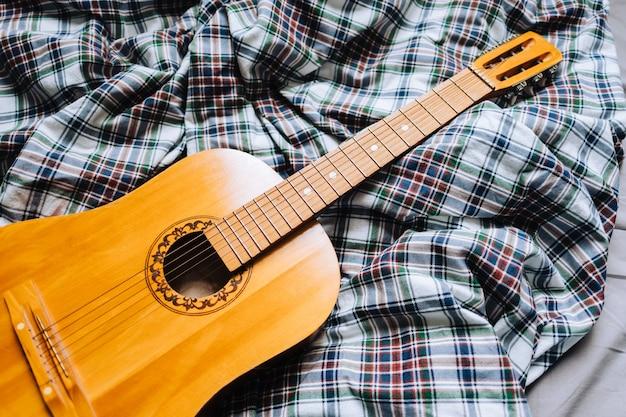 Guitarra acústica de madeira na cama.