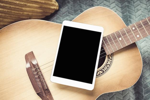 Guitarra acústica e tablet digital em um sofá em um fundo caseiro aconchegante. aulas de música online, aprendendo tocando ou escrevendo músicas e conceito de hobby.