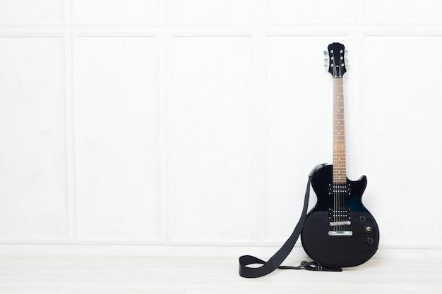 Guitarra apoiada na frente de uma parede branca
