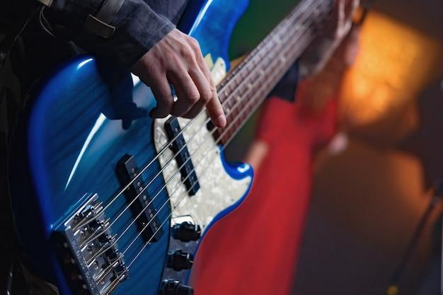 Guitarra baixo nas mãos de um músico