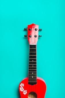 Guitarra clássica acústica vermelha no fundo turquesa