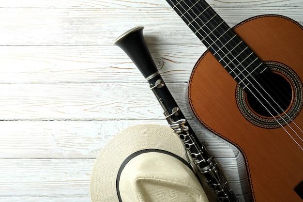 Guitarra clássica, clarinete e chapéu na mesa de madeira branca