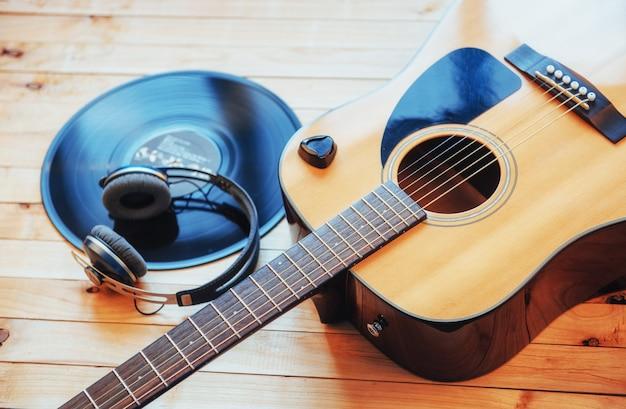 Guitarra clássica com fones de ouvido em um fundo de madeira