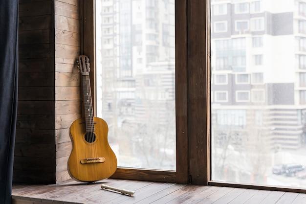 Guitarra clássica e apartamento urbano da cidade moderna