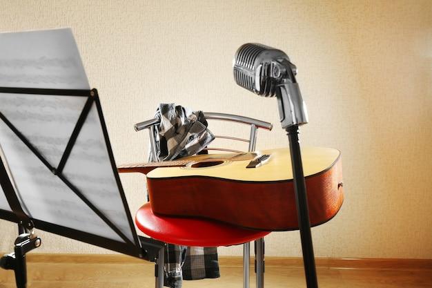 Guitarra com microfone e porta-notas no estúdio, close-up