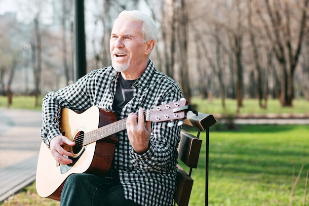 Guitarra como hobby. homem maduro e bonito cantando e tocando violão