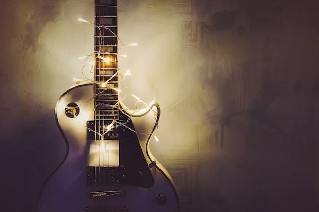 Guitarra de música de feliz natal envolvida por guirlanda colorida como um fundo de presente. guitarra clássica branca no brilho das luzes brilhantes. presente musical para o roqueiro.