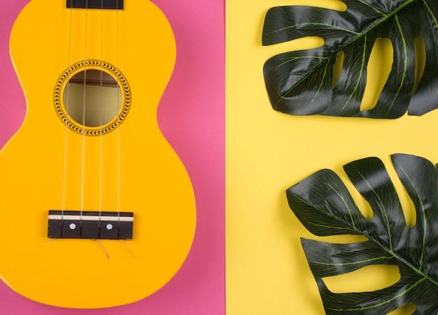 Guitarra de ukulele amarelo brilhante e folhas de monstera