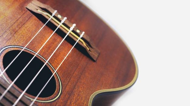Guitarra de ukulele marrom no feriado fundo branco relaxar o tempo de pausa com música