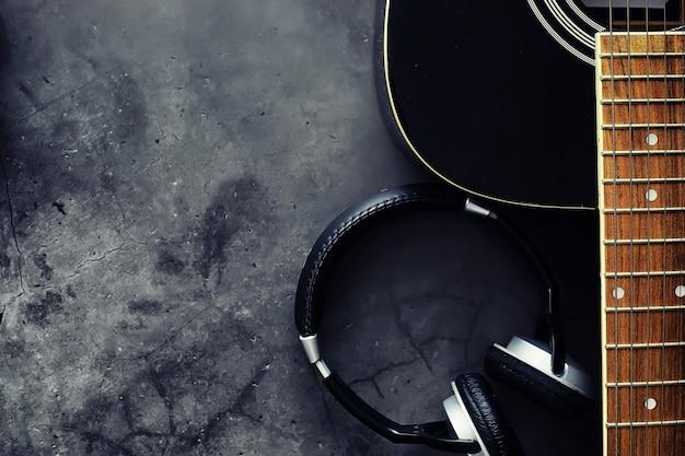 Guitarra e acessórios em um fundo de pedra. músico de mesa, fones de ouvido, microfone e muito mais.