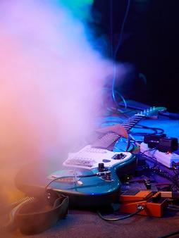Guitarra e equipamento de guitarra mentem no palco no nevoeiro e fumaça na iluminação roxa, azul e laranja.