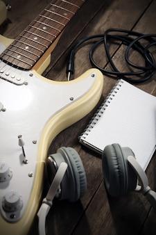 Guitarra elétrica com fones de ouvido e microfone em fundo de madeira