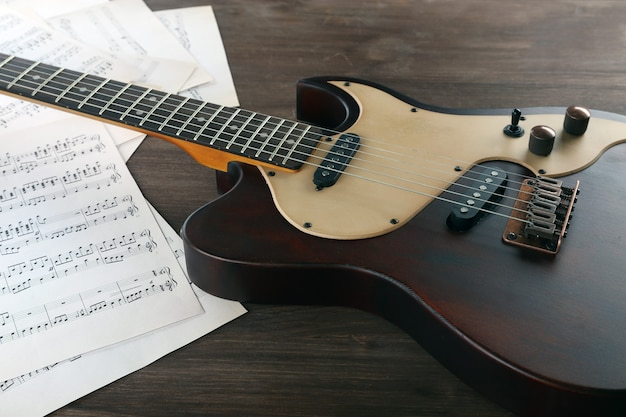Guitarra elétrica com notas musicais em mesa de madeira