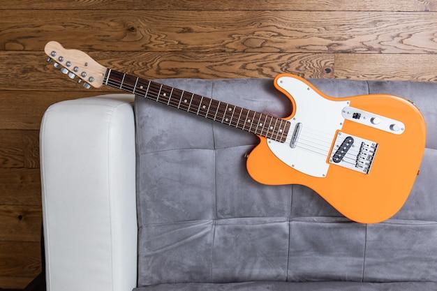 Guitarra elétrica laranja em uma vista superior do sofá de couro, piso de madeira