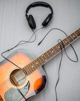 Guitarra, fones de ouvido, silhueta de um guitarrista tocando