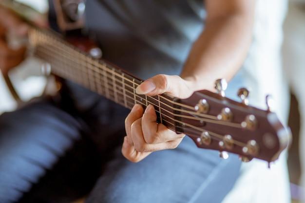 Guitarra-homem que joga a guitarra de madeira no tempo do dia.
